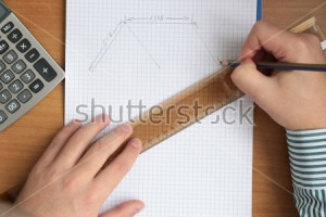 stock-photo-man-hands-working-with-pencil-drawing-roof-on-book-in-a-cage-on-the-wooden-table-with-calculator-582479407